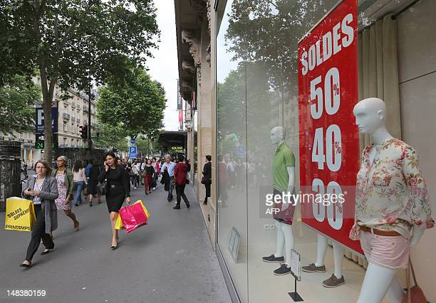 People walk along shop windows of a department store on June 27 in Paris during the official start of the 2012 summer sales The sales period will...