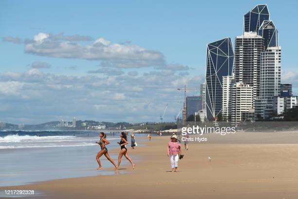 COAST AUSTRALIA APRIL People walk along Surfers Paradise beach on April 07 2020 in Gold Coast Australia A number of major Gold Coast beaches will...