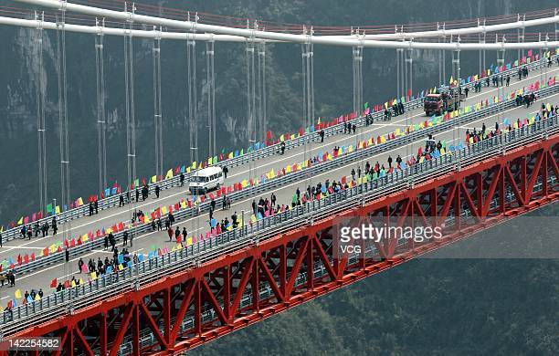 People walk along the Aizhai Suspension Bridge with a main span of over 1100 meters and a height of at least 330 meters on March 31 2012 in Anzhai...
