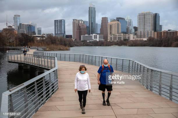 People walk along the Ann and Roy ButlerHike and Bike Trail on March 10, 2021 in Austin, Texas. The City of Austin said it will continue to maintain...