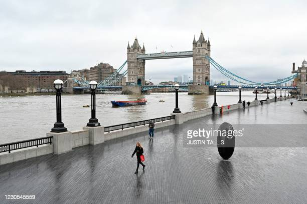 People walk along the bank of the River Thames with Tower Bridge in the background in London on January 12, 2021 as life continues in Britain's third...