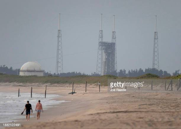 People walk along the beach as an Atlas V rocket carrying Boeing's CST-100 Starliner capsule prepares for a scheduled 1:20 p.m. EDT launch from Space...