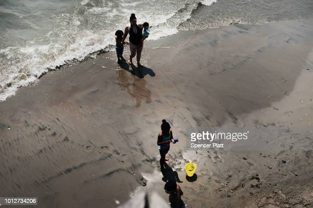 People walk along the beach at Coney Island on a hot summer afternoon on August 7 2018 in the Brooklyn borough of New York City New York City is...