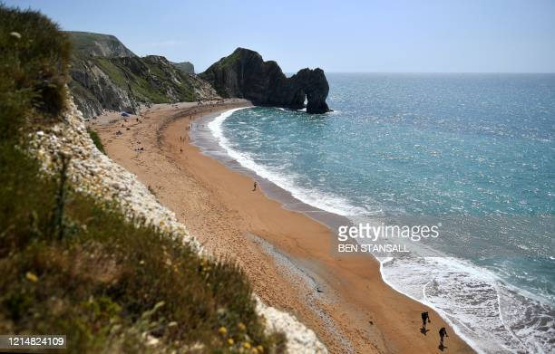 People walk along the beach at the popular tourist spot Durdle Door near West Lulworth on the south coast of England on May 24, 2020. - Travellers...