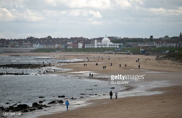 People walk along the beach in Whitley Bay, north east England on April 30 as life in Britain continues during the nationwide lockdown to combat the...