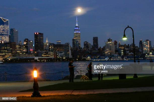 People walk along the boardwalk as the moon rise over the Empire State Building on November 2 2017 in Hoboken NJ