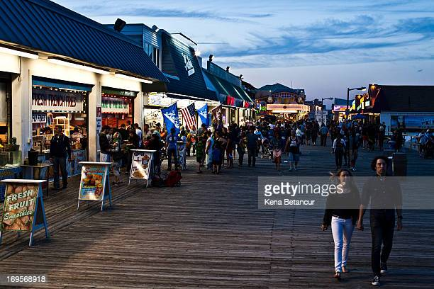 People walk along the boardwalk at Point Pleasant Beach on the first weekend of New Jersey beaches reopening to the public on May 27 2013 in Point...