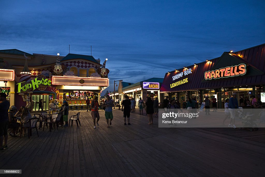 People walk along the boardwalk at Point Pleasant Beach on the first weekend of New Jersey beaches re-opening to the public on May 27, 2013 in Point Pleasant, New Jersey. The region continues to recover and rebuild after Hurricane Sandy devastated parts of the coastline.