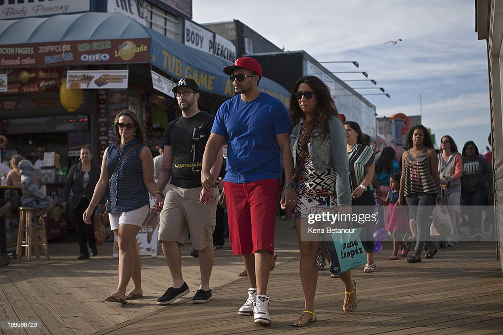 People walk along the broadwalk in Seaside Heights on the first weekend of New Jersey beaches re-opening to the public on May 27, 2013 in Seaside Heights, New Jersey. The region continues to recover and rebuild after Hurricane Sandy devastated parts of the coastline.