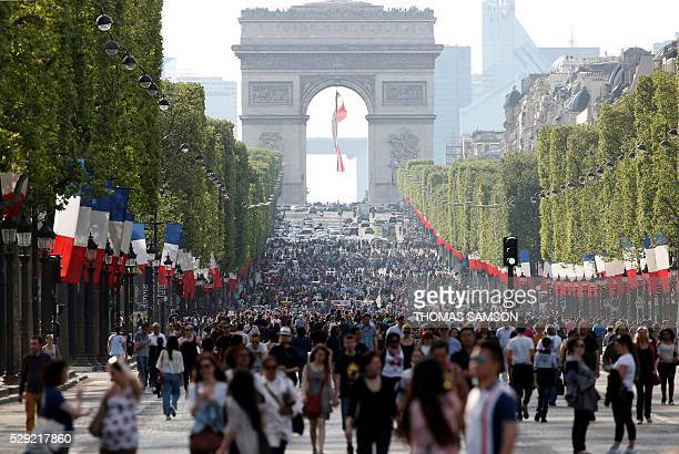 People walk along the Champs Elysees Avenue on May 8 as the French capital's most famous avenue goes carfree for a day in the first instalment of a...