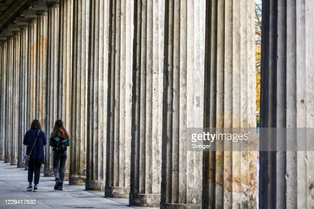 People walk along the column corridor near the Neues Museum on the first day of a four-week semi-lockdown during the second wave of the coronavirus...