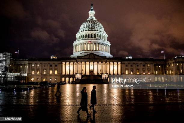People walk along the east front plaza of the US Capitol as night falls on December 17, 2019 in Washington, DC. The House Rules Committee is holding...