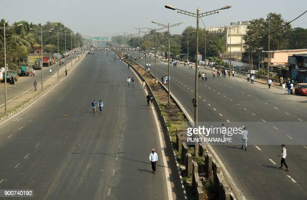 People walk along the Eastern expressway after Republican Party of India supporters blocked the road during a protest in Mumbai on January 3 2018...