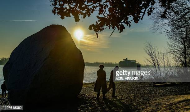 People walk along the Elbe beach in Hamburg, Germany in the light of the setting sun on February 26, 2019. / Germany OUT