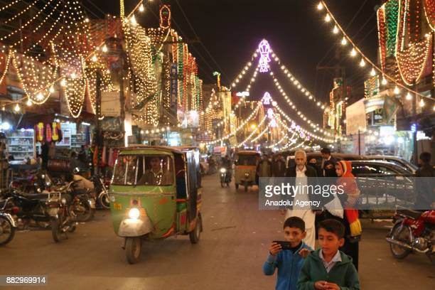 People walk along the illimunated streets during the celebrations for Mawlid alNabi the birth anniversary of Muslims' beloved Prophet Mohammad in...