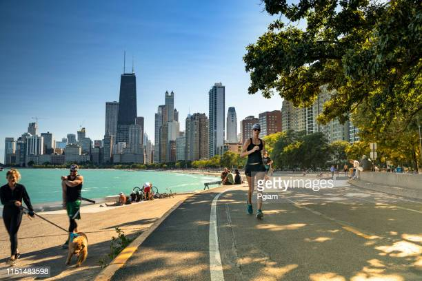 people walk along the lakefront trail in chicago illinois - promenade stock pictures, royalty-free photos & images