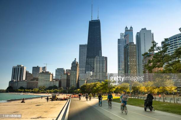 people walk along the lakefront trail in chicago illinois - great lakes stock pictures, royalty-free photos & images