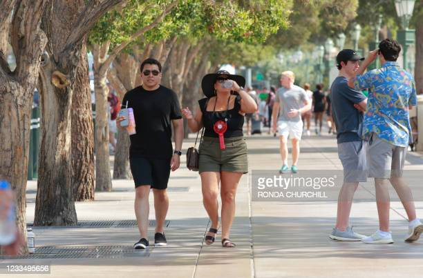 People walk along the Las Vegas Strip during an excessive heat warning, June 16 in Las Vegas, Nevada.