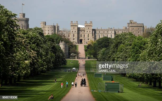 People walk along the Long Walk leading up to Windsor Castle in Windsor, west of London on May 8, 2018. - Britain's Prince Harry and US actress...