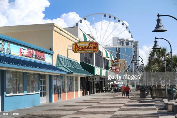 People walk along the Myrtle Beach Boardwalk Promenade ahead of the arrival of Hurricane Florence on September 11 2018 in Myrtle Beach United States...