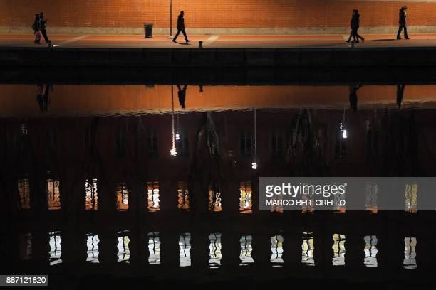 People walk along the Navigli Milan's canals at night on December 6 2017 in Milan / AFP PHOTO / Marco BERTORELLO
