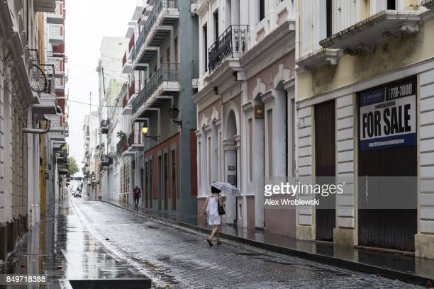 People walk along the nearly deserted streets of Old San Juan as residents prepare for a direct hit from Hurricane Maria on September 19 2017 in San...