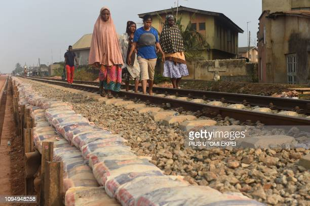 People walk along the new standard gauge railway line under construction from Iju in Lagos to Abeokuta, Ogun State in southwest Nigeria, on February...