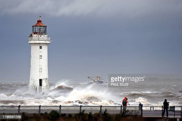 People walk along the promenade as waves in break in a stormy sea alongside the lighthouse in New Brighton north west England on February 9 as Storm...