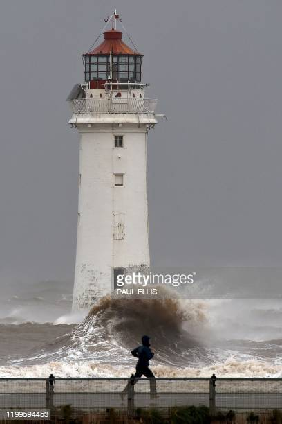 People walk along the promenade as waves in break in a stormy sea alongside the lighthouse in New Brighton, north west England, on February 9 as...