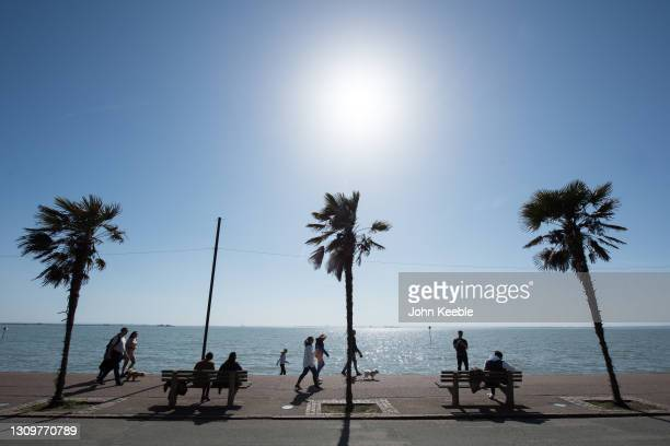 People walk along the promenade beside the beach in the warm weather on March 29, 2021 in Southend, England. Today the government eased its rules...