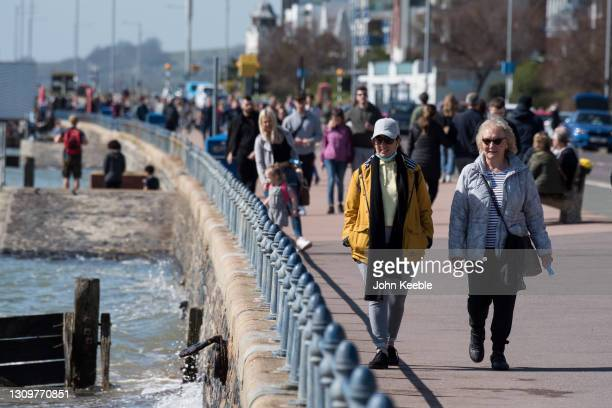 People walk along the promenade in the warm weather on March 29, 2021 in Southend, England. Today the government eased its rules restricting outdoor...