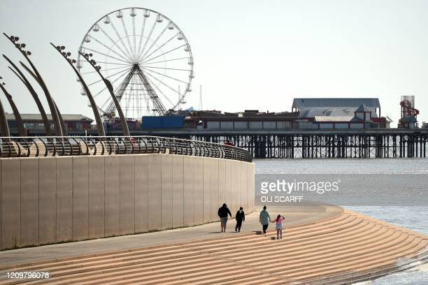 People walk along the promenade toward the central pier in the spring sunshine on the coast in Blackpool northwest England on April 13 during the...