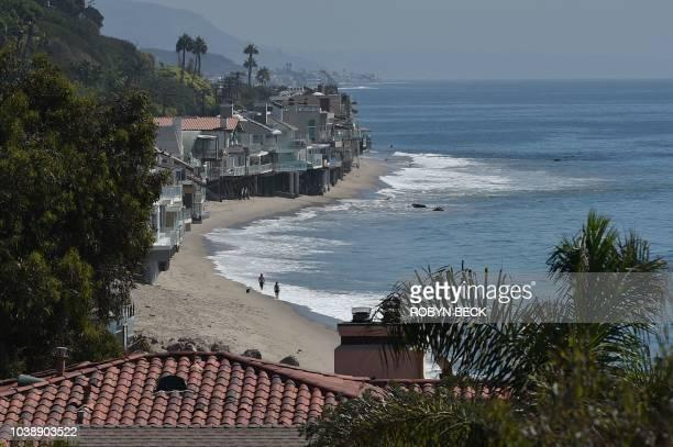 People walk along the public beach past multimillion dollar homes in Malibu California September 18 2018 California's 1976 Coastal Act guarantees...