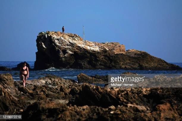 People walk along the rocks at Little Corona Beach on April 15 2020 in Newport Beach California Southern California has seen warmer weather over the...