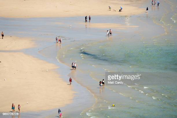 People walk along the sand in the harbour at low tide in St Ives on June 27 2018 in Cornwall England Parts of the UK continue to bask in heatwave...