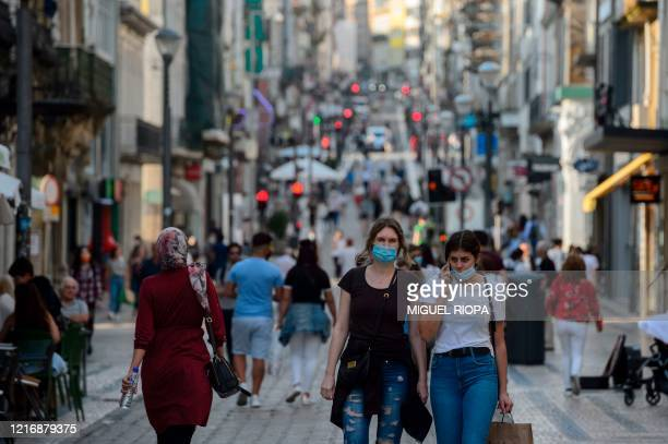 People walk along the Santa Catarina street in downtown Porto on June 1 2020 After a closure of two months and a half due to the coronavirus pandemic...