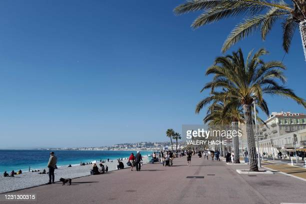 """People walk along the seaside on the """"Promenade des anglais"""" on a sunny day on the French riviera city of Nice, on February 21, 2021. - French health..."""