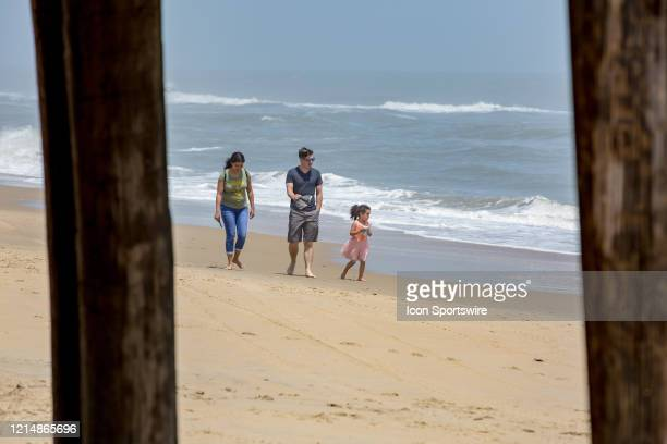People walk along the shoreline near Virginia Beach Fishing Pier to kick off Memorial Day weekend on May 22 in Virginia Beach VA This is the first...