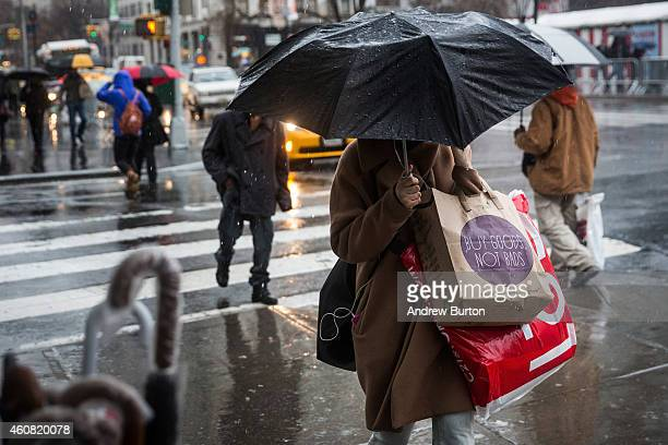 People walk along the sidewalk in the rain on Christmas Eve on December 24 2014 in New York City Recent reports show the US economy grew at 5% in the...