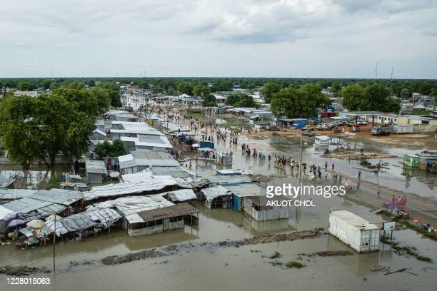 People walk along the street in a flooded area after the Nile river overflowed after continuous heavy rain which caused thousands of people to be...