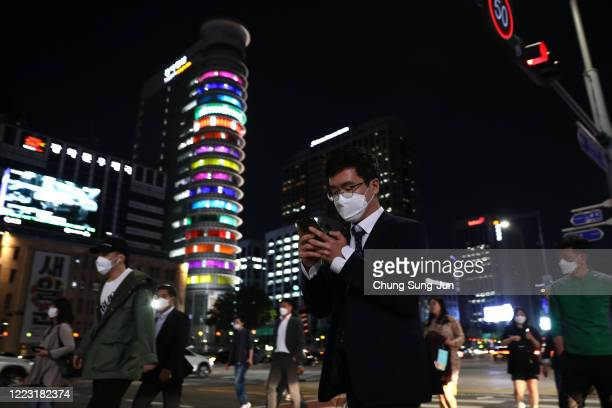 People walk along the street in face masks on May 06 2020 in Seoul South Korea South Korea returned largely to normal as citizens return to their...