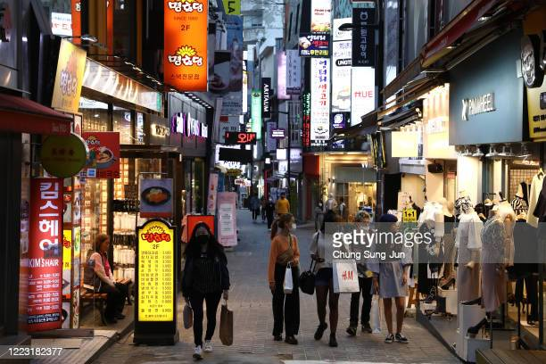People walk along the street in face masks on May 06, 2020 in Seoul, South Korea. South Korea returned largely to normal as citizens return to their...