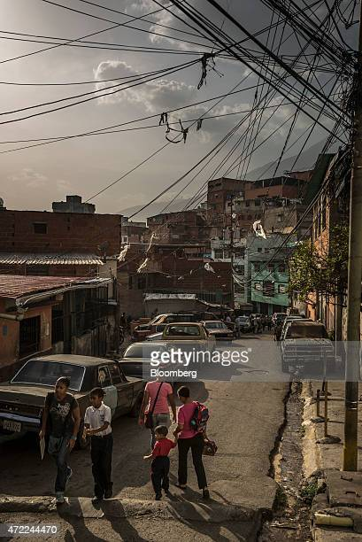 People walk along the street in the Petare neighborhood home to many Colombian immigrants on the outskirts of Caracas Venezuela on Tuesday April 28...
