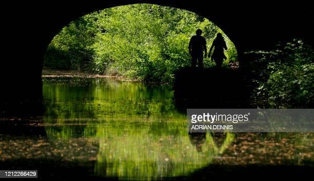 People walk along the tow path of the Basingstoke Canal near Odiham west of London on May 9 as life in Britain continues over the May bank holiday...