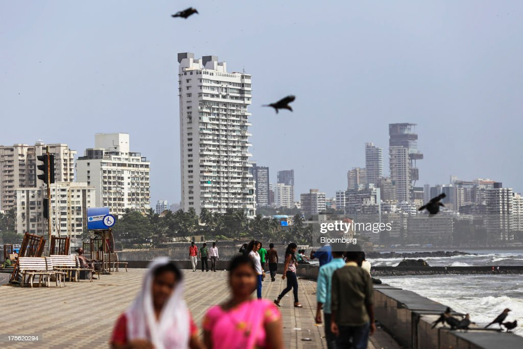People walk along the waterfront as residential and commercial buildings stand in the background in the Cuffe Parade area of Mumbai, India, on Sunday, Aug. 4, 2013. India's purchasing managers index (PMI) services figures for July are scheduled for release on Aug. 5. Photographer: Dhiraj Singh/Bloomberg via Getty Images