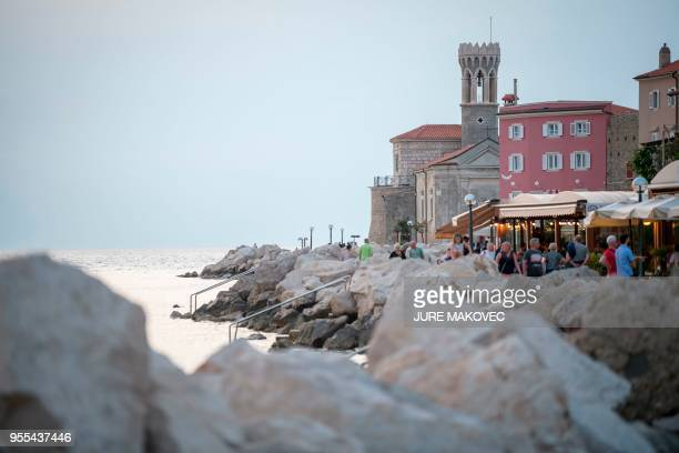 People walk along the waterfront in the Cape Madona area in the coastal town of Piran Slovenia on May 6 2018