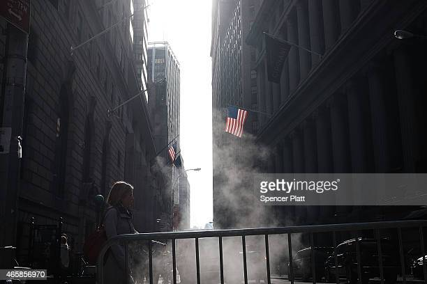 People walk along Wall Street in the financial district on March 11 2015 in New York City Following a Dow Jones industrial average plunge of 300...