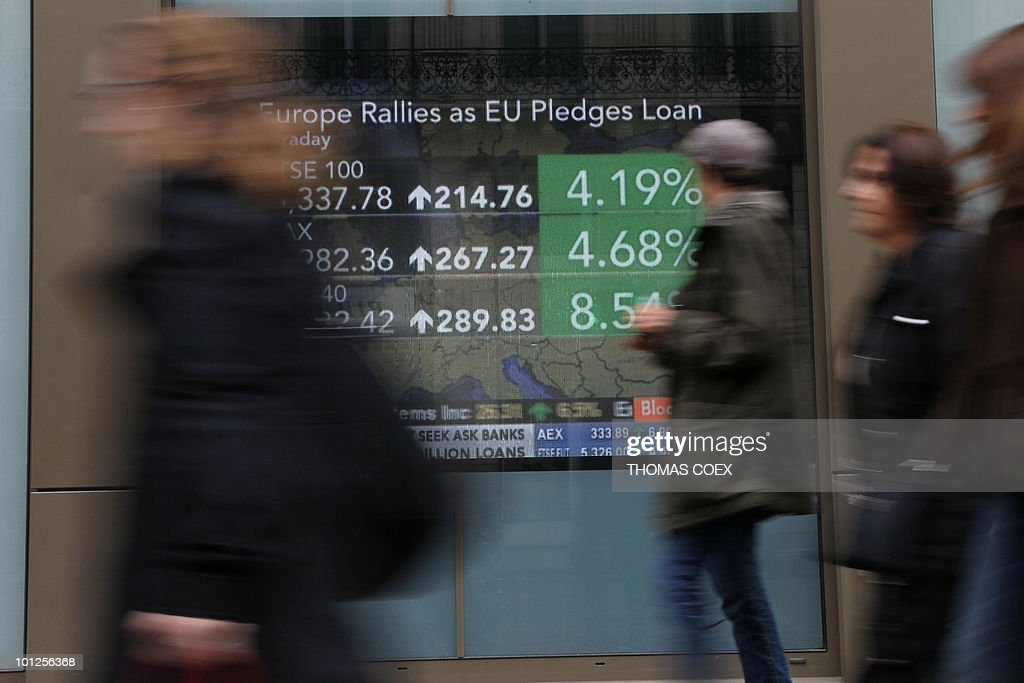 People walk alongside a TV screen displaying European stock markets information in a street of Paris, on May 10, 2010. Stock markets and the euro soared after the EU and IMF agreed a near one-trillion-dollar rescue package for the eurozone, stemming a crisis that threatened to derail global economic recovery.