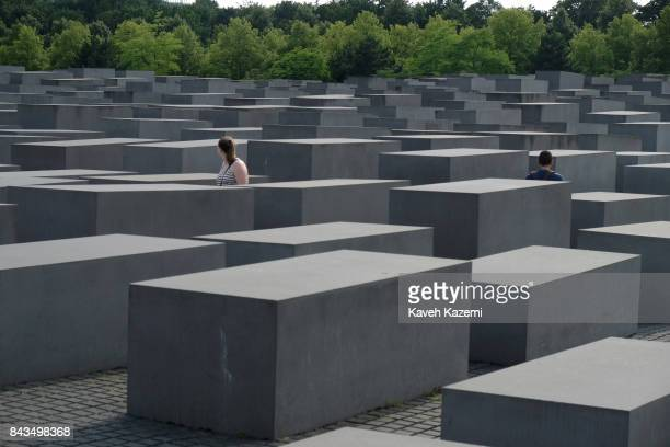 People walk amid concrete slabs or 'stelae' in The Memorial to the Murdered Jews of Europe also known as the Holocaust Memorial designed by architect...
