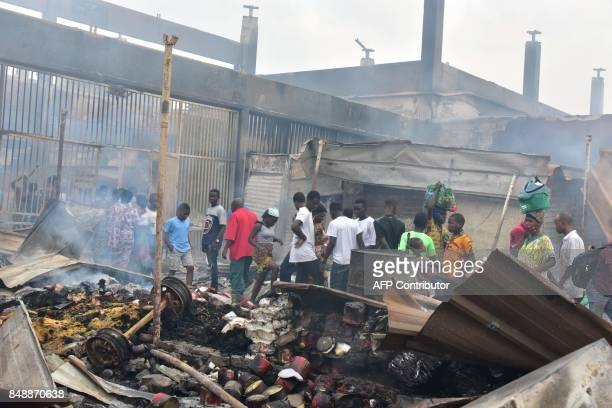 People walk amid debris in the market after a fire devastated the building during the night on September 18 2017 in Abobo neighborhood of Abidjan /...